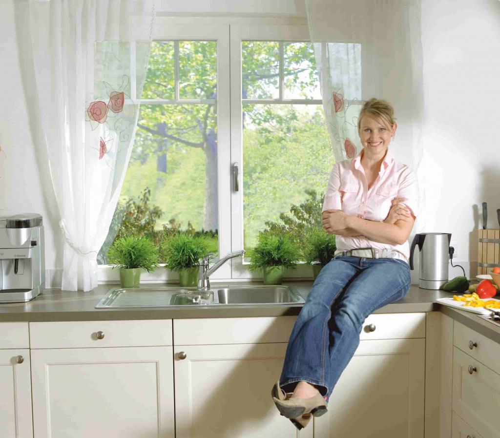 Kunststofffenster in der Küchenzeile mit stolzer Hausbesitzerin