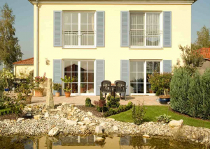 Kunststofffenster zieren die Fassade eines Hauses mit Gartenanlage und Teich