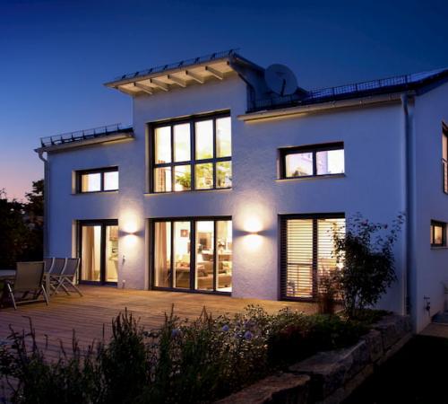 Beleuchtetes Haus bei Nacht mit Holz Aluminium Fenstern